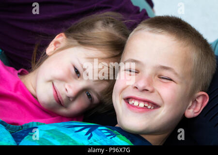 Close-up portrait of two small cute blond happily smiling children, brother and sister, boy and girl laying in bed under colorful blanket. Careless in - Stock Photo