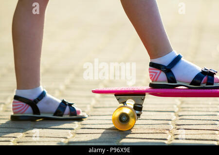 Child slim legs in white socks and black sandals on plastic pink skateboard on bright sunny summer blurred copy space pavement background. Outdoors ac - Stock Photo
