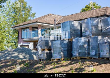 FLODA, SWEDEN - JULY 15 2018: Detached house undergoing home improvement and landscaping with front garden filled with building supplies such as brick - Stock Photo