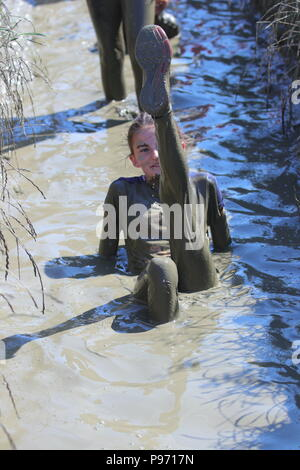 A young girl crawls through sludge during the Young Mudders Obstacle Course , where participants can choose to take on the 2.5k or 5k course in Leeds - Stock Photo