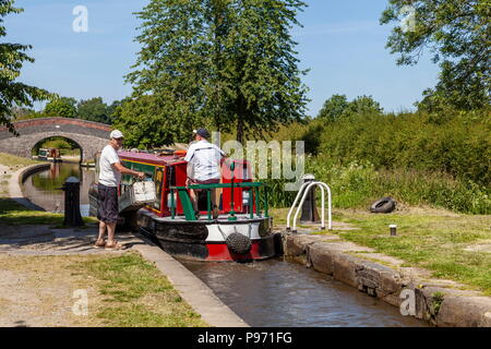 A Personwaits to close the lock gates while a narrow boat leaves New Marton Top Lock on the Llangollen Canal - Stock Photo