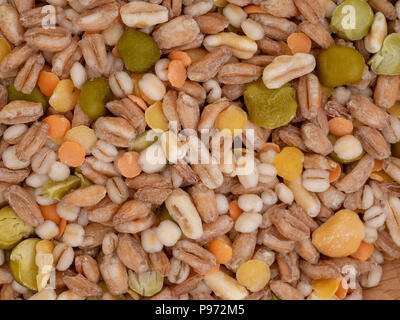 Assorted grains and pulses mix full background, top view. Winter food includes split peas, red and yellow lentils, pearl barley, kamut, spelt. - Stock Photo
