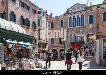 Campo Santi Apostoli and the Antico Doge Hotel, Cannaregio, Venice, Veneto, Italy with a news agent selling souvenirs and tourists - Stock Photo