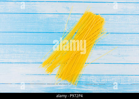 Uncooked Italian Pasta With Strap On Blue And White Painted Background With Empty Space High Contrast Top View - Stock Photo