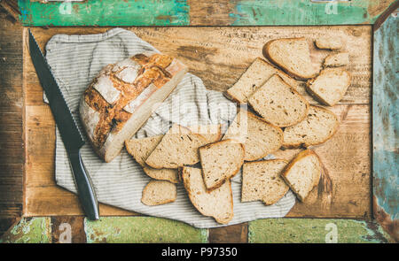 Flat-lay of sourdough wheat bread cut in slices in tray - Stock Photo