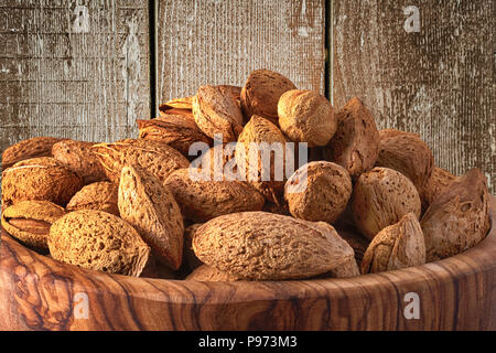 Almonds in wooden bowl on wooden background. - Stock Photo