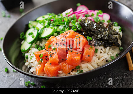 Hawaiian salmon fish poke bowl with rice, radish,cucumber, tomato, sesame seeds and seaweeds. Buddha bowl. Diet food - Stock Photo