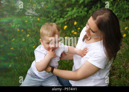 Young pregnant girl sits on lawn in city park. Mother supports her son. Little boy bites his finger. Happy motherhood. Blur effect - Stock Photo