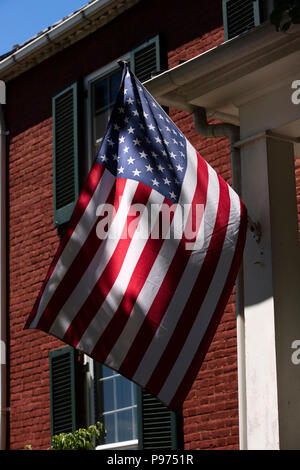 American flag flying in front of brick building in Upperville Virginia in Fauquier County - Stock Photo