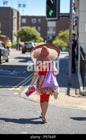 Brighton UK 15th July 2018 - This lady wears a huge sunhat to stay in the shade in Brighton as the temperatures soar into the low 30s in some parts of the South East of Britain today Credit: Simon Dack/Alamy Live News - Stock Photo