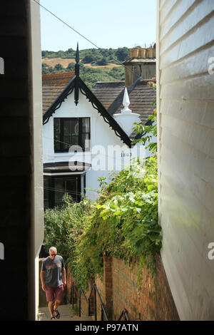 Hastings, UK -July 14 2018: A man seen walking  through a narrow walkway in the Old Town in the fishing port of Hastings on a hot summers day as the temperatures sore to above 27 degrees on 14 July 2018.  Hastings on the south coast of England is 53 miles south-east of London and is 8 miles from where the  Battle of Hastings took place in October 1066. Credit: David Mbiyu Credit: david mbiyu/Alamy Live News - Stock Photo