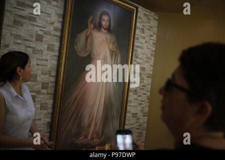 Managua, Nicaragua. 15th July, 2018. A woman prays before the image of Jesus which was hit by bullets in the Divine Mercy chapel, in Managua, Nicaragua, 15 July 2018. A large group of parishioners approached today the parish of the Divine Mercy of Managua, where last Friday a group of students asking for the resignation of President Daniel Ortega was besieged by paramilitaries, to clean it and return the order. Credit: Rodrigo Sura/EFE/Alamy Live News - Stock Photo