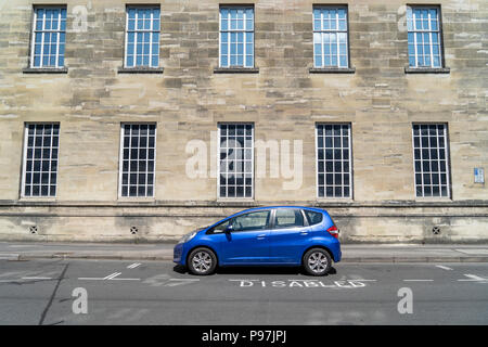 Blue car parked in disabled parking bay - Stock Photo