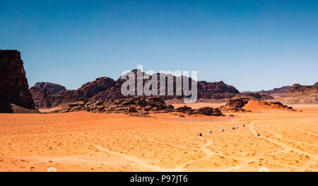 Convoy of 4x4 vehicles and tracks in desolate expanse of Wadi Rum desert valley with mountains, Jordan, Middle East - Stock Photo