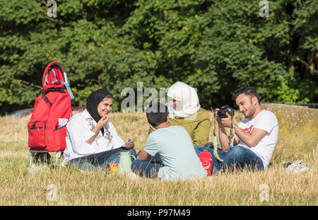 Asian family eating (having a picnic, picnicking) outside in the British countryside in East Sussex, England, UK. - Stock Photo