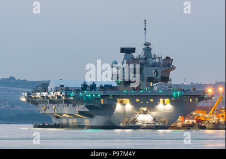 HMS Queen Elizabeth Aircraft Carrier, the Royal Navy's largest and newest warship, moored at dusk in the docks at Portsmouth, Hampshire, England, UK. - Stock Photo