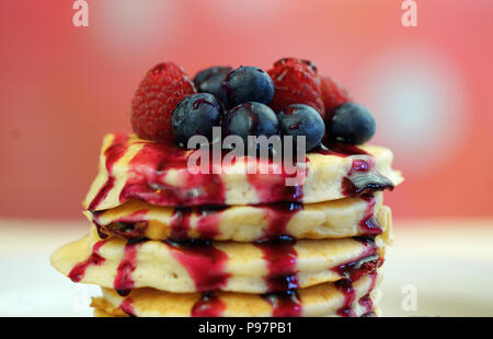 Stack of pancakes with raspberries, blueberries and drizzled with blueberry maple syrup, macro closeup. - Stock Photo