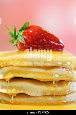 Stack of pancakes with strawberry on top and drizzled with syrup, macro closeup. - Stock Photo