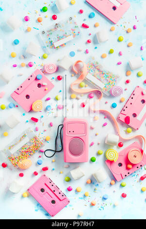 Cassette tapes and retro radio player in a pastel colour flat lay with candies, bonbons, marmalade and bubble gum. Sweet music concept with copy space. Vanilla palette - Stock Photo