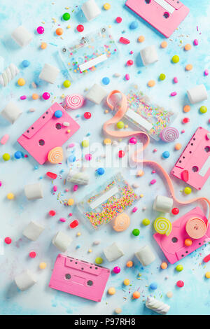 Pink cassette tapes in a sweet sounds concept. Candies, sprinkles and marmalades on a light background with copy space. Pastel color flat lay - Stock Photo