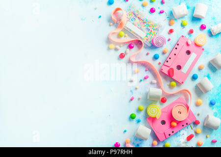 Pink cassette tapes in a sweet sounds concept. Candies, sprinkles and marmalades on a light background with copy space. Pastel color flat lay header - Stock Photo