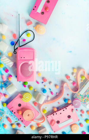 Candy cassette tapes in a pleasant music concept. Candies, sprinkles and marmalades on a light background with copy space. Pastel color flat lay - Stock Photo