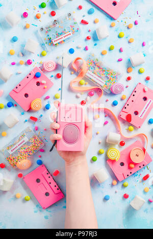 Candy cassette tapes and pink retro radio player in a hand. Candies, sprinkles and marmalades in a pleasant music concept with copy space. Pastel color flat lay with sweets - Stock Photo