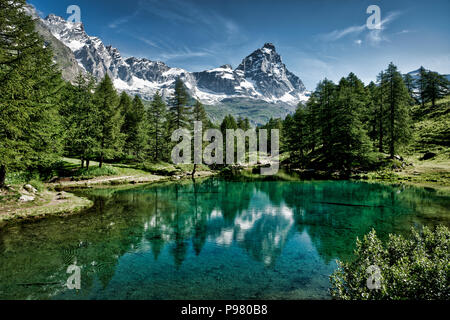 The blue lake and the Matterhorn in a scenic summer landscape with sunny lights seen from Breuil-Cervinia, Aosta Valley - Italy - Stock Photo