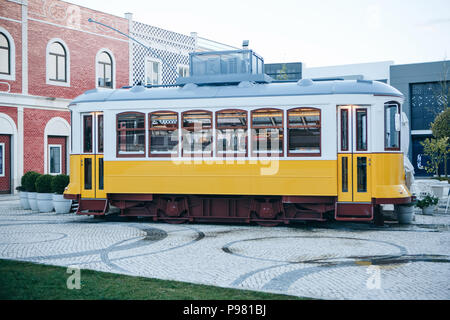 Lisbon, June 18, 2018: An original and authentic street cafe in the old-fashioned traditional Portuguese yellow tram next to the fashion outlet called - Stock Photo
