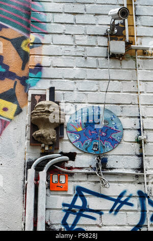 Berlin, Friedrichshain, RAW Gelände. CCTV surveillance camera, street art and old electrical wiring on exterior of old industrial building - Stock Photo