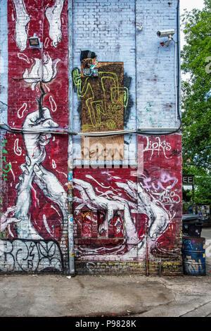 Berlin, Friedrichshain, RAW Gelände. CCTV Surveillance camera points at running man street art on old industrial building - Stock Photo