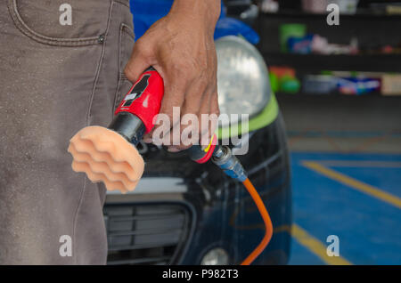 Man holds a polisher car headlights - Stock Photo