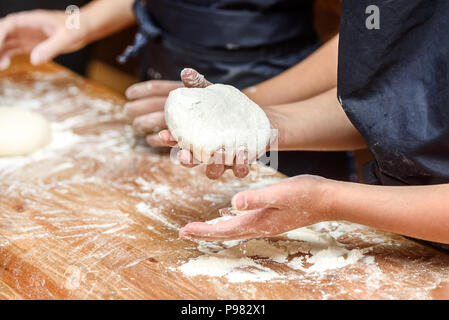 Close-up of children's hands preparing dough for pizza. Pizza, children and the concept of cooking - children make pizza. - Stock Photo