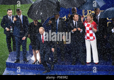 Victory ceremony under umbrellas: Vladimir Putin (President of the Russian Federation) walks from the podium, Emmanuel Macron (President of France) and Kolinda Grabar-Kitarovic (President of Croatia) stand in the rain and laughs. GES / Football / World Championship 2018 Russia, Final: France - Croatia, 15.07.2018 GES / Soccer / Football, Worldcup 2018 Russia, Final: France vs Croatia, Moscow, July 15, 2018 | usage worldwide - Stock Photo