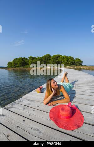 Attractive young woman lying on wooden track in morning leisure - Stock Photo