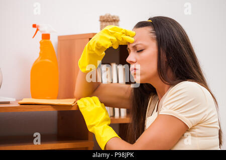 Young woman is cleaning the furniture in the house. She is tired. - Stock Photo