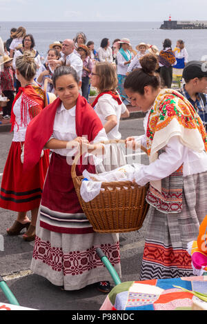 Ponta Delgada, Azores, Portugal - 07/07/2018 - two young girls wearing traditional dress, holding a wicker basket - Divine Holy Spirit celebration - Stock Photo
