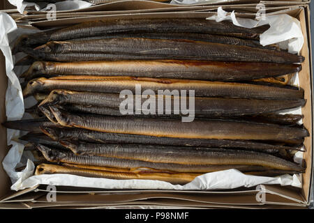 Fresh smoked eels in a cardboard box for sale - Stock Photo