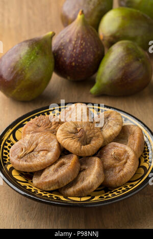 Dish with dried figs and ripe fresh ones on the background - Stock Photo