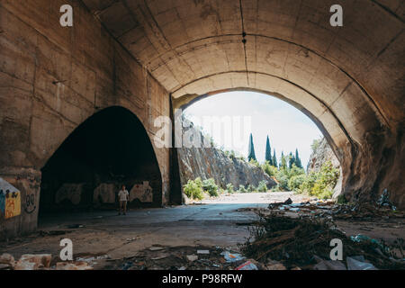 a tourist explores an abandoned aircraft hangar in the mountainside at Mostar Airport, Bosnia and Herzegovina - Stock Photo