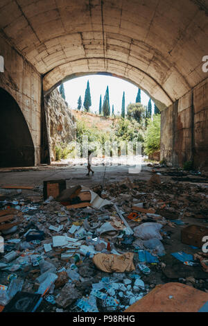 a tourist stands inside an abandoned aircraft hangar in the mountainside at Mostar Airport, Bosnia and Herzegovina - Stock Photo