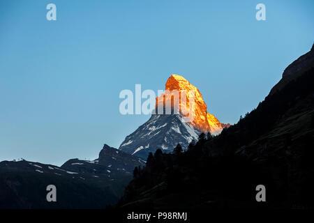 View of the iconic snow-capped peak of the Matterhorn mountain viewed from Zermatt, Valais, Switzerland as morning sun lights the summit - Stock Photo