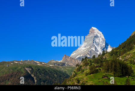 View of the iconic snow-capped peak of the Matterhorn mountain and foothills viewed from Zermatt, Valais, Switzerland with clear blue sky - Stock Photo