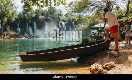 a lifeguard watches over the Kravica waterfall lake - a tufa cascade in Bosnia and Herzegovina, during the busy summer - Stock Photo