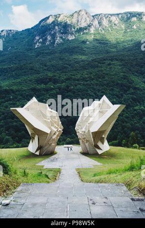 two tourists are dwarfed by the big white Tjentište spomenik (Yugoslav war memorial monument) in the Sutjeska National Park, Bosnia and Herzegovina - Stock Photo