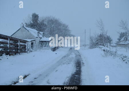 Snow falling on a minor road near Lairg in the Scottish Highlands - Stock Photo