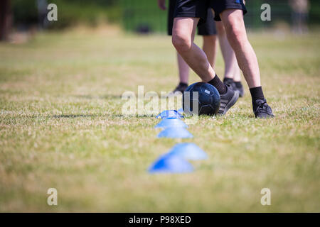 Three schoolboys practicing football soccer skills on a playing field UK - Stock Photo