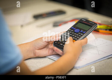 Secondary aged school pupil using an electronic calculator in a math lesson uk - Stock Photo
