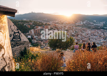 a young group of tourists sit atop Bunquers del Carmel at sunset, a famous lookout over the city of Barcelona, Spain - Stock Photo