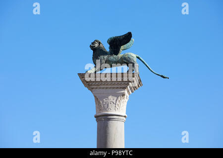 Winged Lion statue, symbol of Venice in a sunny day, blue sky in Italy - Stock Photo
